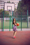 Beautiful young woman playing basketball outdoors Royalty Free Stock Image