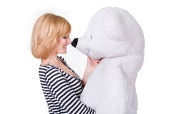 Beautiful young woman playing with big white teddy Royalty Free Stock Photography