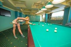 Beautiful young woman playing billiards Stock Photos