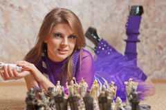 Beautiful young woman playing chess Stock Photography