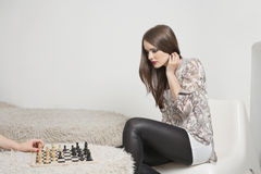 Beautiful young woman playing chess Stock Photos
