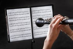 Beautiful young woman playing clarinet Stock Images