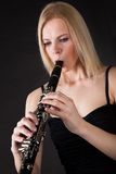 Beautiful young woman playing clarinet Stock Image