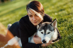 Beautiful young woman playing with funny husky dog with different eyes outdoors at park on green grass. Beautiful young woman playing with funny husky dog Stock Images