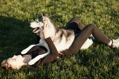 Beautiful young woman playing with funny husky dog  outdoors in park. Beautiful young woman playing with funny husky dog Royalty Free Stock Images