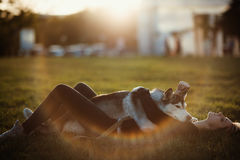 Beautiful young woman playing with funny husky dog outdoors in park at sunset  or sunrise Royalty Free Stock Photography