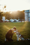 Beautiful young woman playing with funny husky dog outdoors in park at sunset  or sunrise. Beautiful young woman playing with funny husky dog Royalty Free Stock Photography