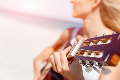 Beautiful young woman playing guitar on beach Stock Image