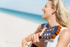 Beautiful young woman playing guitar on beach Stock Photography