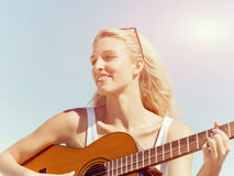 Beautiful young woman playing guitar on beach Stock Images
