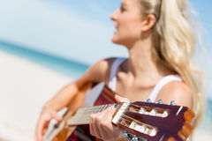 Beautiful young woman playing guitar on beach Royalty Free Stock Photo
