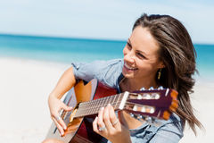 Beautiful young woman playing guitar on beach. Beautiful young smiling woman playing guitar on beach Stock Images