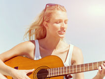 Beautiful young woman playing guitar on beach Royalty Free Stock Photos