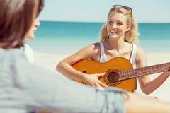 Beautiful young woman playing guitar on beach Stock Photos