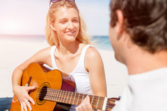 Beautiful young woman playing guitar on beach Stock Photo