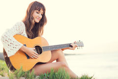 Beautiful young woman playing guitar on beach. At sunset, fashion lifestyle Royalty Free Stock Photography