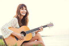 Beautiful young woman playing guitar on beach. At sunset, fashion lifestyle Stock Photo