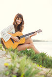 Beautiful young woman playing guitar on beach Stock Photo