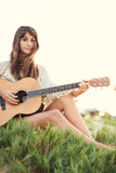 Beautiful young woman playing guitar on beach Royalty Free Stock Image