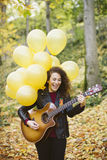 Beautiful young woman playing guitar on forest. Royalty Free Stock Images