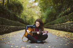 Beautiful young woman playing guitar sitting on the forest. Girl wearing black jacket and sunglasses, fashion lifestyle Royalty Free Stock Photography