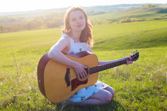 Beautiful young woman playing guitar at sunset Stock Images