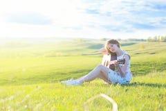 Beautiful young woman playing guitar at sunset Royalty Free Stock Photo