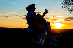 Beautiful young woman playing guitar at sunset Stock Photography