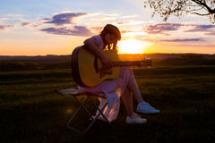 Beautiful young woman playing guitar at sunset Stock Image