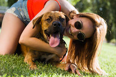 Beautiful young woman playing with her dog in the park. Stock Photos