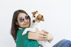 Beautiful young woman playing with her little cute dog at home. Lifestyle portrait. Love for animals concept. white background. Pet happy puppy backgrounds stock images