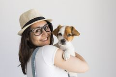 Beautiful young woman playing with her little cute dog at home. Lifestyle portrait. Love for animals concept. white background. Beautiful young woman playing stock photography