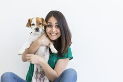 Beautiful young woman playing with her little cute dog at home. Lifestyle portrait. Love for animals concept. white background. Pet happy puppy backgrounds royalty free stock photography