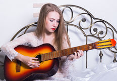 Beautiful young woman playing music on a bed with happiness and guitar stock photography