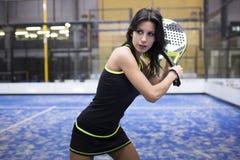 Beautiful young woman playing paddle tennis indoor. Stock Photos