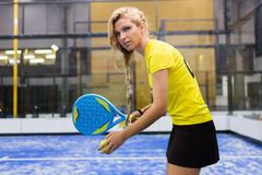 Beautiful young woman playing paddle tennis indoor. royalty free stock images