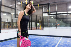 Beautiful young woman playing paddle tennis indoor. royalty free stock image