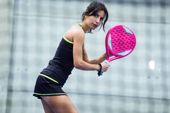 Beautiful young woman playing paddle tennis indoor. Royalty Free Stock Photo