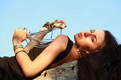 Beautiful young woman playing with pearl necklace laying on a rock Stock Photo