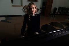 Beautiful Young Woman Playing the Piano Stock Photo