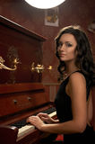 Beautiful young woman playing the piano Royalty Free Stock Photos
