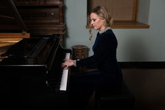 Beautiful Young Woman Playing the Piano Royalty Free Stock Photo