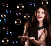 Beautiful young woman playing with soap bubbles Royalty Free Stock Photography