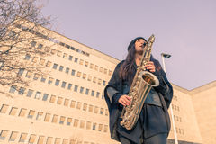 Beautiful young woman playing tenor saxophone Royalty Free Stock Photos