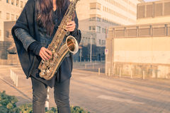 Beautiful young woman playing tenor saxophone Stock Images