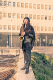 Beautiful young woman playing tenor saxophone Royalty Free Stock Images