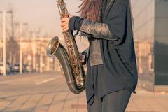 Beautiful young woman playing tenor saxophone Stock Photography