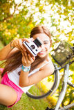 Beautiful young woman playing with a vintage camera Royalty Free Stock Images