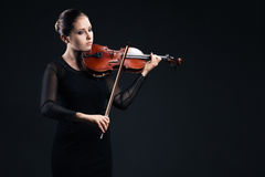 Beautiful young woman playing violin over black Royalty Free Stock Image