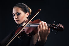 Beautiful young woman playing violin over black Stock Images